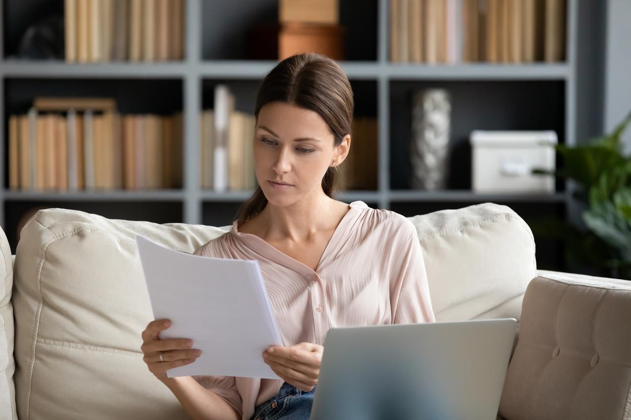 Une femme comparant son contrat d'expatriation avec un exemple.